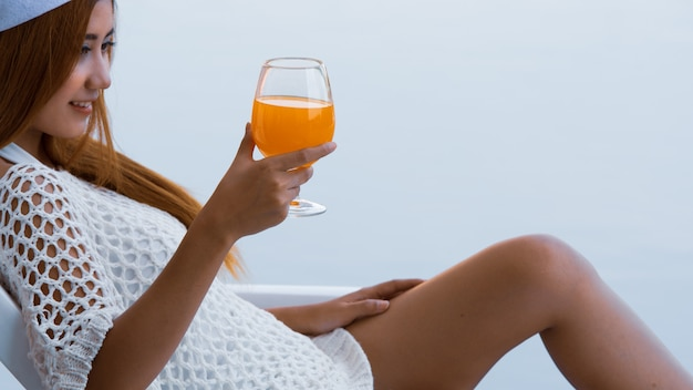 オレンジジュースのグラスを持って若いアジア女性がプールでビーチチェアでリラックス。