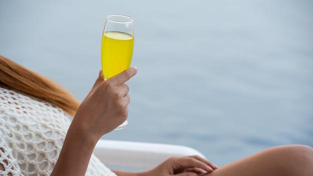 パイナップルジュースのグラスを持って若いアジア女性がプールでビーチチェアでリラックス。