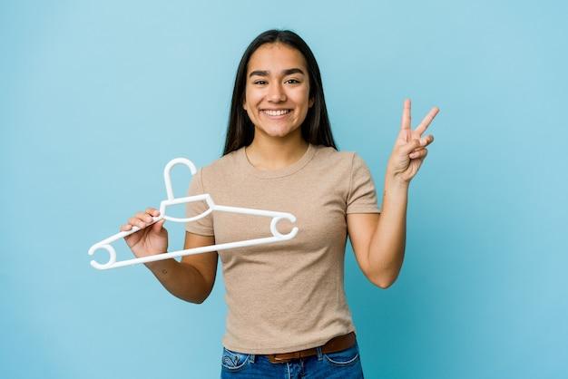 青い壁に隔離されたハンガーを持っている若いアジアの女性は、指で平和のシンボルを喜んで気楽に示しています。