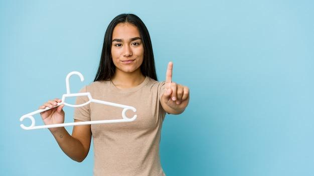 指でナンバーワンを示す青い壁に分離されたハンガーを保持している若いアジアの女性。