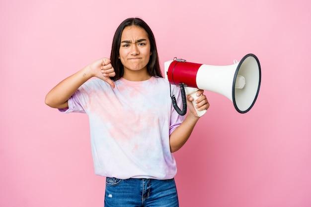 싫어하는 제스처, 엄지 손가락을 보여주는 분홍색 배경에 고립 된 확성기를 들고 젊은 아시아 여자. 불일치 개념.