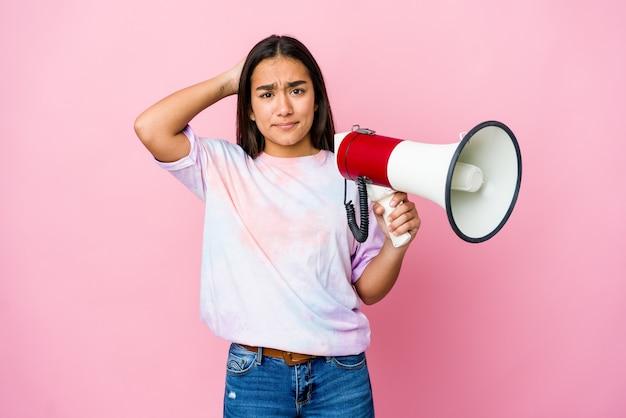 충격을 받고 분홍색 벽에 고립 된 확성기를 들고 젊은 아시아 여자, 그녀는 중요한 회의를 기억했다