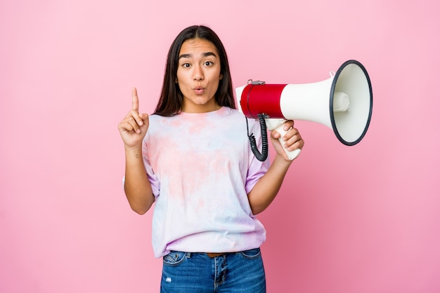 몇 가지 좋은 아이디어, 창의성의 개념을 갖는 분홍색 벽에 고립 된 확성기를 들고 젊은 아시아 여자