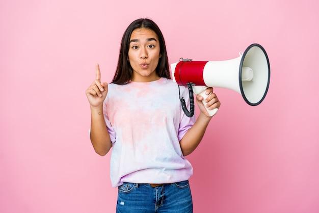 몇 가지 좋은 아이디어, 창의성의 개념을 갖는 분홍색 벽에 고립 된 확성기를 들고 젊은 아시아 여자. 프리미엄 사진