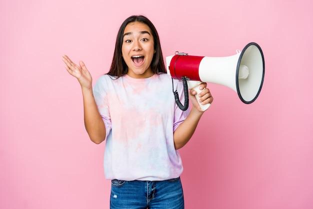 즐거운 놀라움을 받고, 흥분하고 손을 올리는 분홍색 벽에 고립 된 확성기를 들고 젊은 아시아 여자