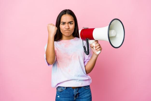 카메라, 공격적인 표정에 주먹을 보여주는 분홍색 벽에 고립 된 확성기를 들고 젊은 아시아 여자