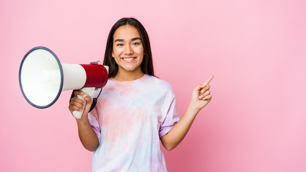 웃 고 옆으로 가리키는, 빈 공간에서 뭔가 보여주는 분홍색 벽에 고립 된 확성기를 들고 젊은 아시아 여자.