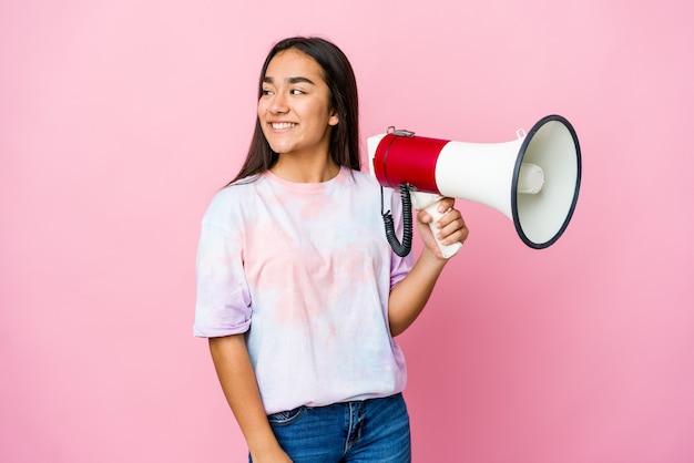 Молодая азиатская женщина, держащая мегафон, смотрит в сторону улыбаясь, веселая и приятная. Premium Фотографии