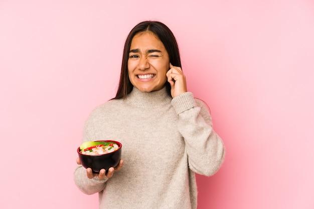 Молодая азиатская женщина, держащая лапшу, изолировала уши руками
