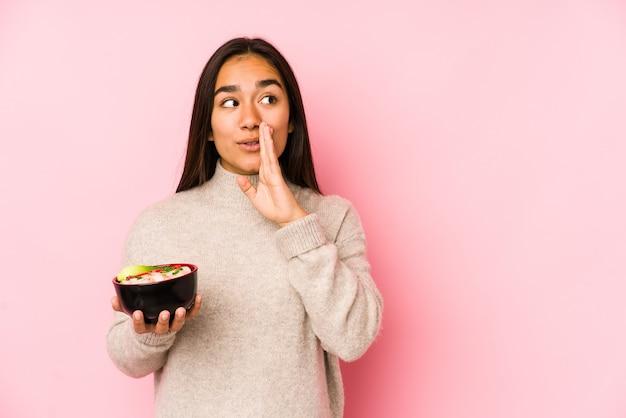 孤立した麺を持っている若いアジアの女性は秘密のホットブレーキニュースを言って脇を見ています