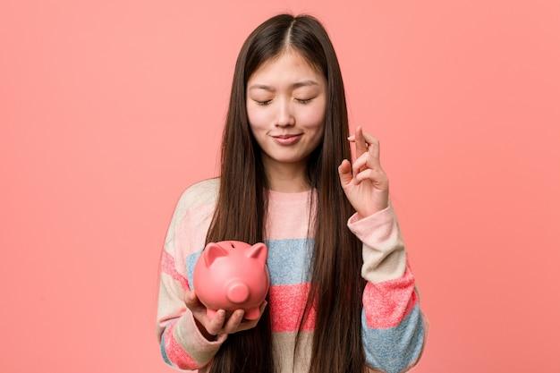 행운을 위해 돼지 저금통 횡단 손가락을 들고 젊은 아시아 여성