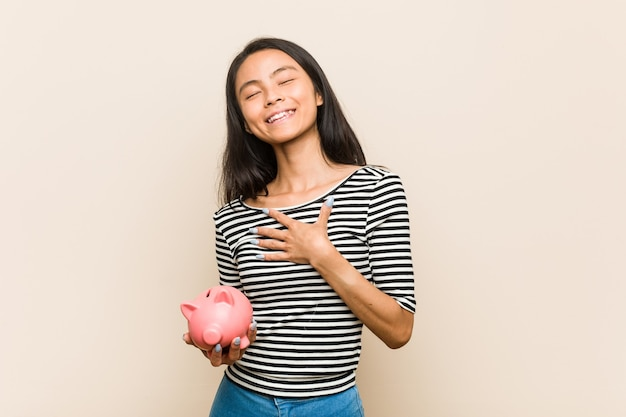 貯金箱を持っている若いアジアの女性は、胸に手を置いて大声で笑います。