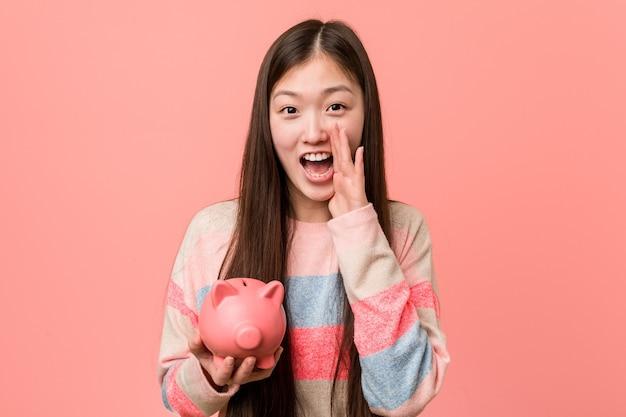前面に興奮して叫んでいる貯金箱を保持している若いアジア女性。