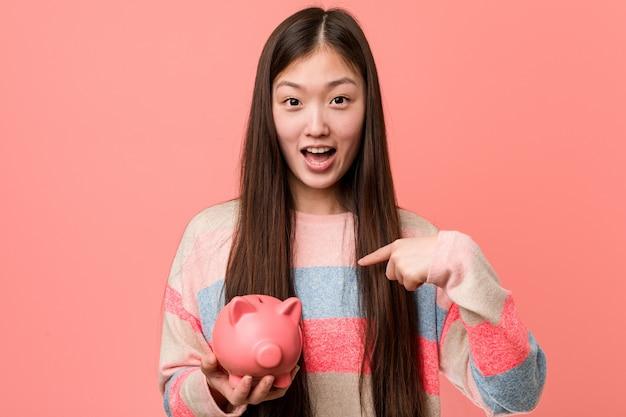 돼지 저금통을 들고 젊은 아시아 여자는 자신을 가리키는 웃 고 크게 웃 고.