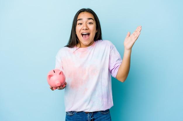 즐거운 놀라움을 받고, 흥분하고 손을 올리는 고립 된 벽 위에 분홍색 은행을 들고 젊은 아시아 여자