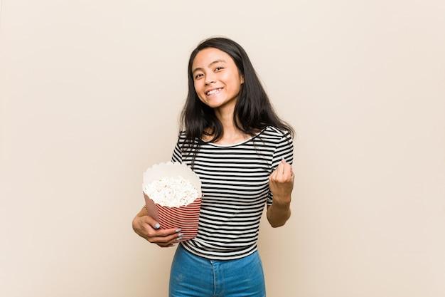 Молодая азиатская женщина держа восхищаться ведра попкорна веселя беззаботный и. концепция победы.