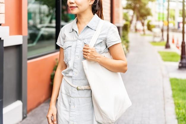 재사용 가능한 가방을 들고 도시에서 걷는 젊은 아시아 여성, 제로 폐기물 개념