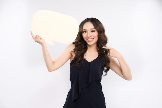 白い背景の上の吹き出しを保持している若いアジアの女性