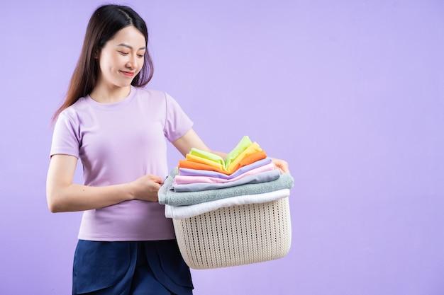 紫色の背景に服のスタックを保持している若いアジアの女性