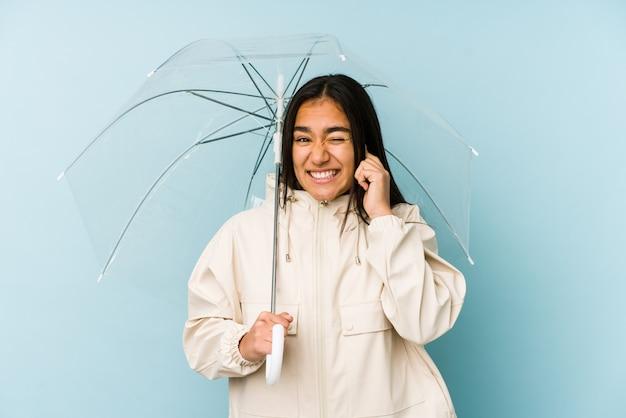 手で耳を覆う傘を保持している若いアジア女性。