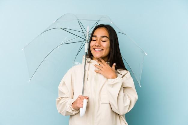 우산을 들고 젊은 아시아 여자는 큰 소리로 가슴에 손을 유지 웃음