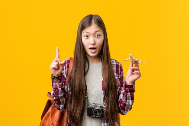 Young asian woman holding a airplane icon having some great idea, concept of creativity.
