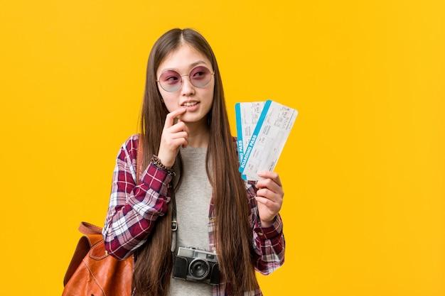 항공 티켓을 들고 젊은 아시아 여자 복사 공간을보고 뭔가 대해 생각을 편안합니다.