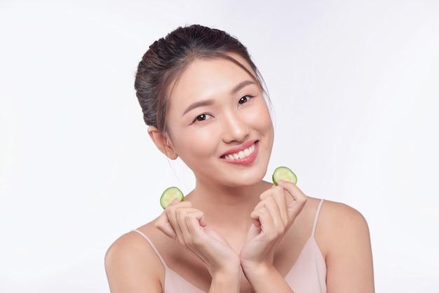 分離された彼女の手でキュウリのスライスを保持して食べる若いアジア女性