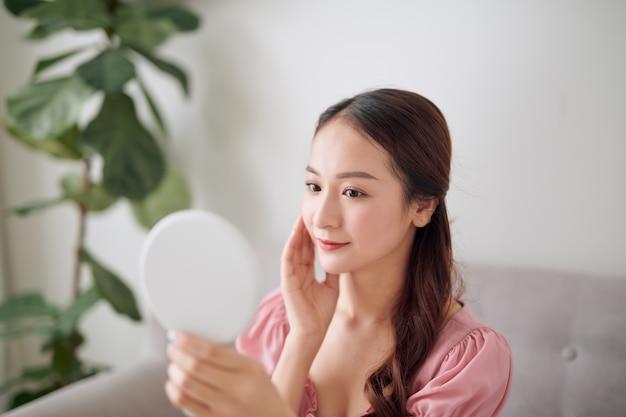 젊은 아시아 여자 잡고 거실에서 거울을보고