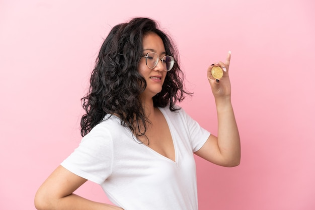 Young asian woman holding a bitcoin isolated on pink background suffering from backache for having made an effort
