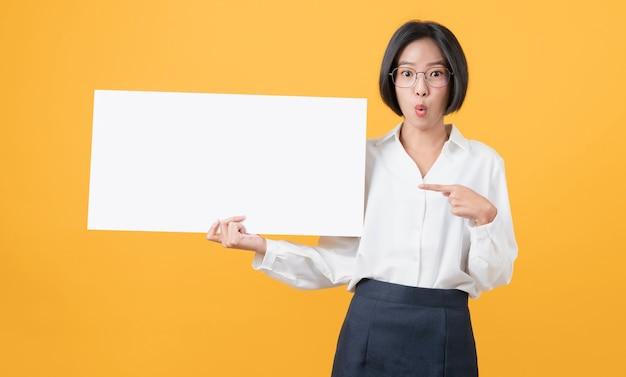 웃는 얼굴로 빈 종이를 들고 주황색 배경을 바라보는 젊은 아시아 여성. 광고 표지판용.
