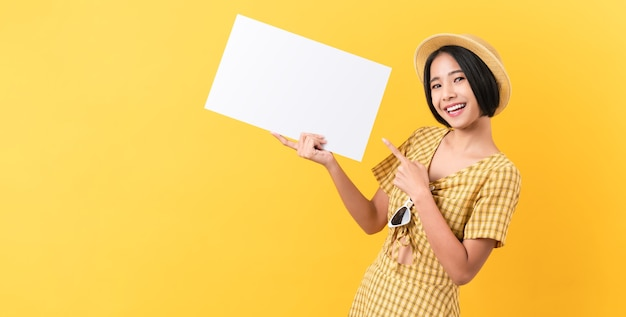 笑顔と黄色の背景で白紙を保持している若いアジアの女性
