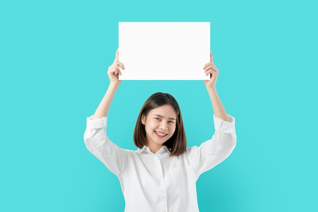 Young asian woman holding blank paper with smiling face and looking on the blue background