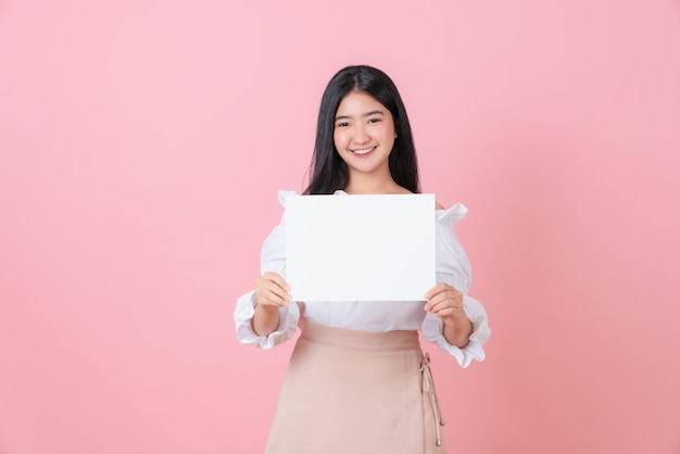 Young asian woman holding blank paper with smiling face and looking on the pink background. for advertising signs.