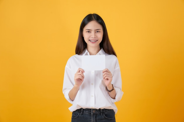 Young asian woman holding blank paper with smiling face and looking on the yellow wall. for advertising signs.
