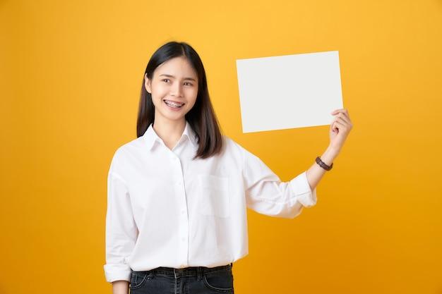 Молодая азиатская женщина, держащая чистый лист бумаги с улыбками.