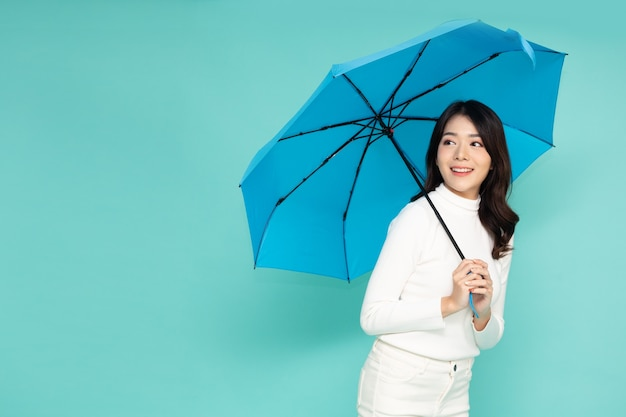 Young asian woman holding blue umbella standing isolated on green background