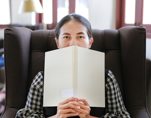 ライブラリに顔の本を持っている若いアジアの女性。