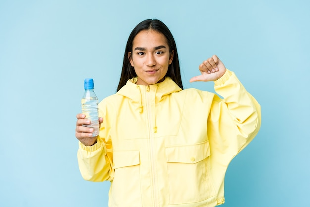 Young asian woman holding a bottle of water isolated on blue wall feels proud and self confident, example to follow.