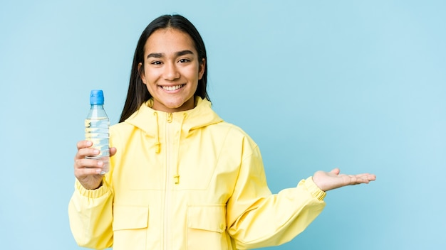 Young asian woman holding a bottle of water isolated on blue wall showing a copy space on a palm and holding another hand on waist.