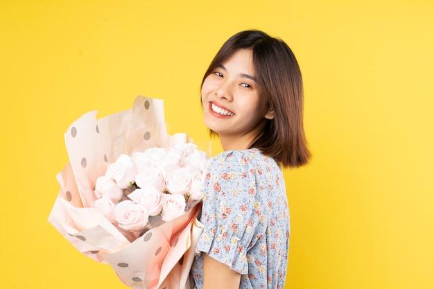 黄色の背景に花束を保持している若いアジアの女性