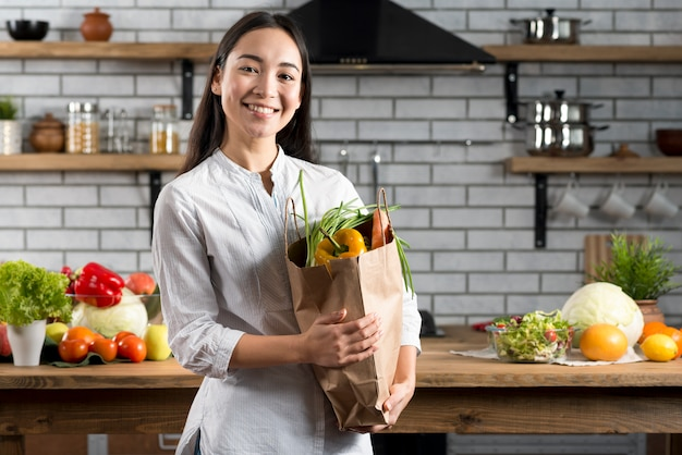 Young asian woman holding brown grocery bag with vegetables