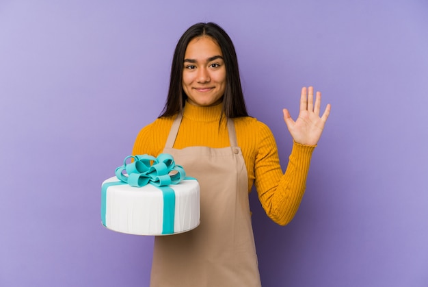 Young asian woman holding a cake smiling cheerful showing number five with fingers.
