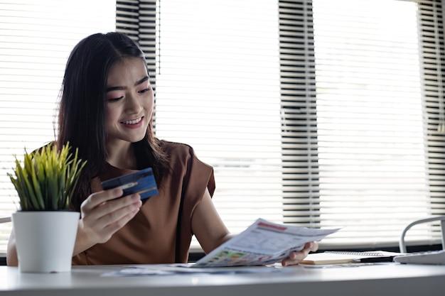 Молодая азиатская женщина, держащая кредитную карту и счет с улыбкой на рабочем столе в доме. женщины счастливо улыбаются после того, как нет долгов. не беспокойтесь о проблемах, связанных с задолженностью по кредитной карте.