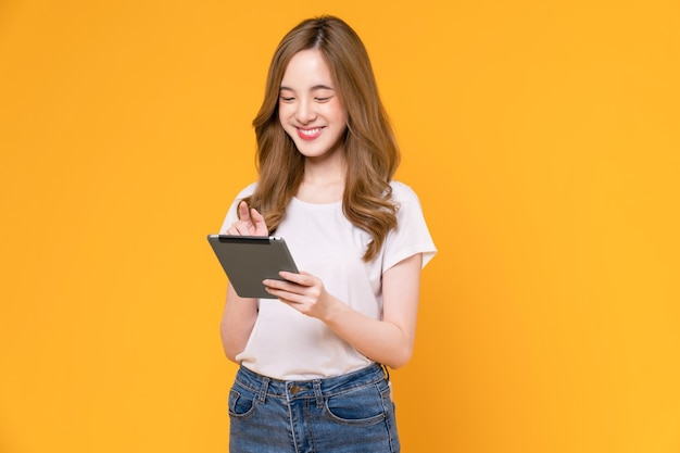 Молодая азиатская женщина, держащая цифровой планшет и улыбающаяся сенсорным экраном, светло-желтый фон