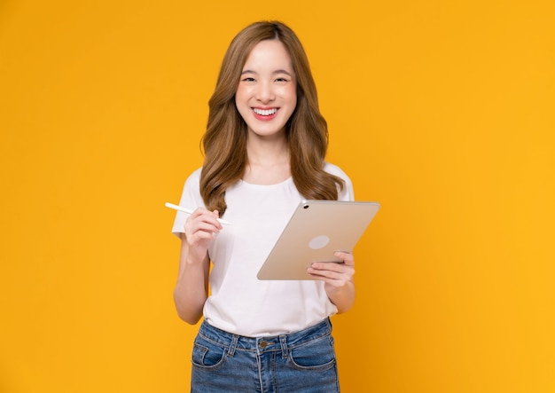 Young asian woman holding digital tablet and smiling with touch on screen, light yellow background.