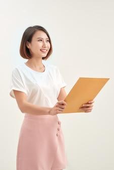 求人応募用のドキュメント封筒を保持している若いアジアの女性