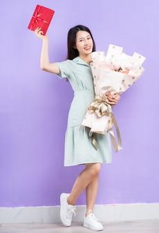 紫色の背景にギフトボックスと花を保持している若いアジアの女性