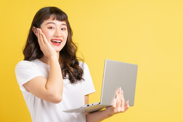 Young asian woman holding laptop on yellow