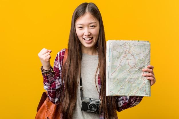 Young asian woman holding a map cheering carefree and excited. victory concept.